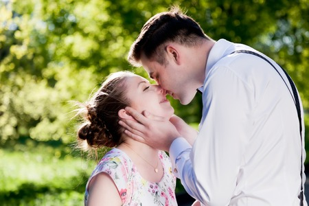 touching face: Young romantic couple kissing with love in summer park. Dating, fiance with fiancee, romance. Stock Photo