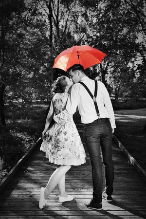 Young romantic couple in love flirting in rain, man holding red umbrella. Dating, romance, black and white photo