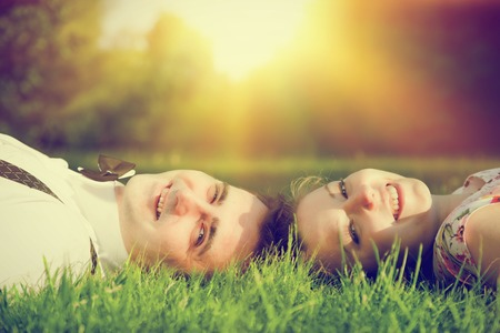 couple dating: Happy couple in love smiling while lying on summer grass. Dating, romantic mood, sun light. Stock Photo
