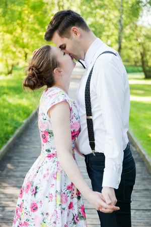 hold hands: Young couple in love holding hands and looking each other in the eyes in summer park , straight wooden path. Woman in dress and man wearing shirt with suspenders.