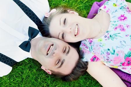 Happy couple in love lying on summer grass and smiling. View from above photo
