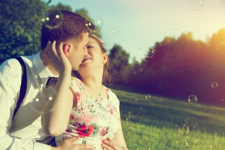 Young romantic couple kissing with love in sunny summer park. Dating, fiance with fiancee, elegant romance. Vintage, soap bubbles photo