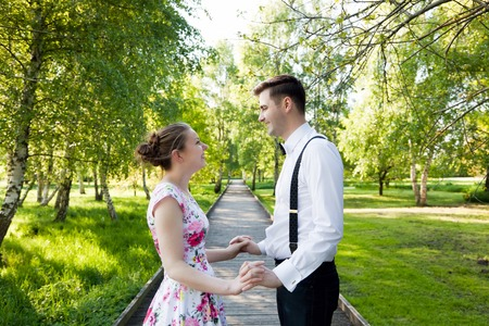 Young couple in love holding hands and looking each other in the eyes in summer park , straight wooden path. Woman in dress and man wearing shirt with suspenders. photo