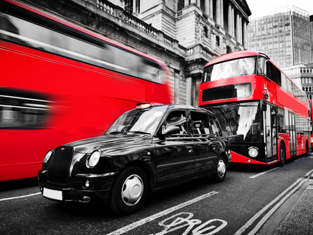 Symbols of London, the UK. Red buses and black taxi cab in motion. Black and white with red. Iconic English transportation, famous double decker