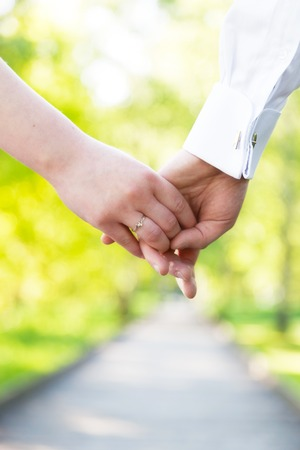 fiancee: Holding hands close-up. Couple in love dating in summer park. Woman in dress and man wearing elegant shirt. View from the back. Date, fiance with fiancee, hand in hand concepts