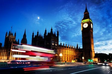 Red Bus in Bewegung, Big Ben und Westminster Palace in London, Großbritannien. in der Nacht. Blick von Westminster Bridge. Mond scheint auf dunklen blauen Himmel Lizenzfreie Bilder