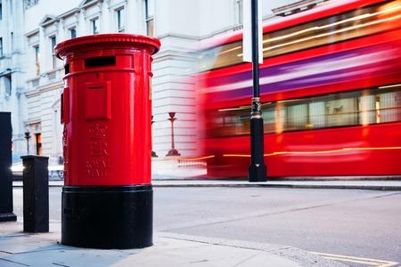 buzon: Tradicional buzón de correo rojo y el autobús rojo en movimiento en Londres, Reino Unido. Los símbolos de la ciudad y de Inglaterra
