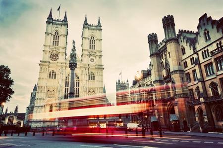 ウェストミン スター寺院教会のファサードは、赤バスがロンドンに移動します。イギリス、イギリスのシンボル。ヴィンテージ、レトロなスタイル 写真素材