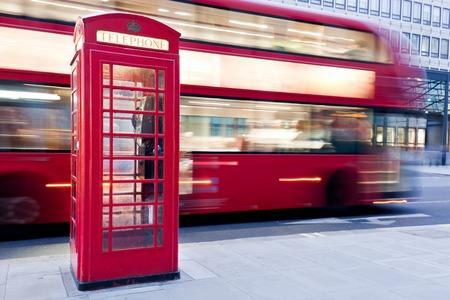 cabina telefonica: Londres, Reino Unido. Cabina de teléfono roja y autobús rojo que pasa en el desenfoque de movimiento. Símbolos de la Gran Bretaña, Reino Unido, Inglaterra.