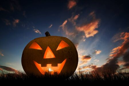 carved pumpkin: Halloween pumpkin glowing under dark sunset, night sky. Hand carved jack olantern with scary face