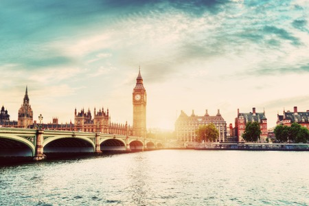 some: Big Ben, Westminster Bridge on River Thames in London, the UK. English symbol. Sunset sky with some clouds. Vintage Stock Photo