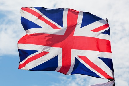 united kingdom: The Union Jack, the national flag of the United Kingdom waving on wind against blue sky