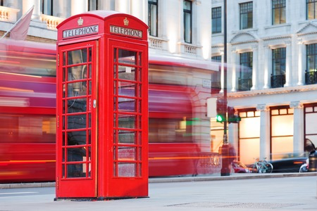 telephone booth: London, UK. Red telephone booth and red bus passing in motion blur. Symbols of Great Britain, United Kingdom, England. Stock Photo