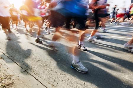Los corredores de maratón en movimiento. Ejecutarse en la ciudad, el sol brilla.