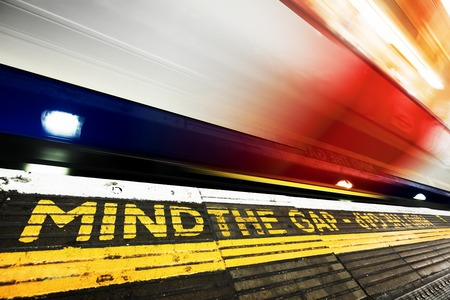 London underground, tube. Mind the gap sign painted on the floor. Train speeding in motion. Transportation Editorial