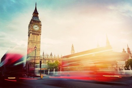 London, the UK. Red buses in motion and Big Ben, the Palace of Westminster. The symbols of England in vintage, retro style