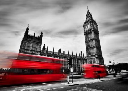 Londen, het Verenigd Koninkrijk. Rode bussen in beweging en de Big Ben, het paleis van Westminster. De iconen van Engeland in zwart-wit met rode kleur. Stockfoto