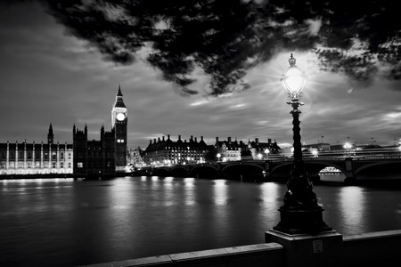 Big Ben, The Palace of Westminster and River Thames at night, London, the UK. Retro street lamp light. Wind moving trees. Black and white