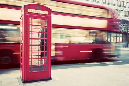 London, UK. Red telephone booth and red bus passing in motion blur. Symbols of Great Britain, United Kingdom, England. Vintage