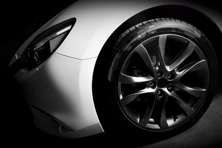 Luxury sports car close up of aluminium rim and headlight. Garage