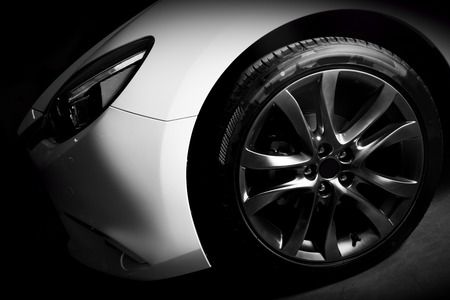 tire: Luxury sports car close up of aluminium rim and headlight. Garage