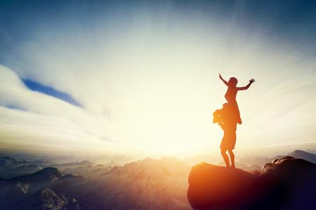 Glückliche Paare, die auf dem Dach der Welt! Mann hält Frau an seinen Armen zusammen genießen Sonnenuntergang auf dem Gipfel des Berges.