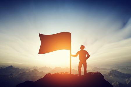 excitación: Hombre orgulloso levantando una bandera en el pico de la montaña. Concepto de desafío con éxito, nuevo logro