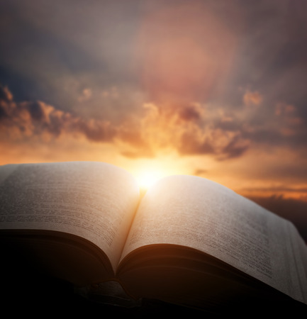 gods: Open old book, light from the sunset sky, heaven. Fantasy, imagination, education, religion concept. Stock Photo