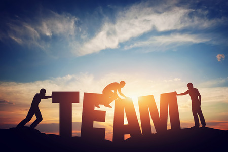 connecting: People connect letters to compose the team word. Teamwork concept, idea. Sunset positive light. Stock Photo