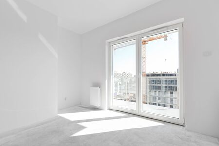 white window: Empty new apartment room for interior arrangement. Light from the window, white walls, concrete floor