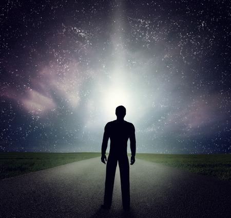 El hombre de pie por sí sola en el camino mirando el cielo nocturno, universo, estrellas fugaces. Sueño, aventura, futuro, explorar conceptos Foto de archivo - 46658225