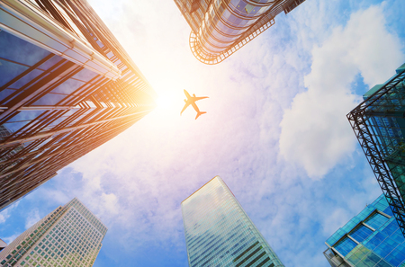 sun: Airplane flying over modern business skyscrapers, high-rise buildings. Transport, transportation, travel. Sun light on blue sky. Stock Photo