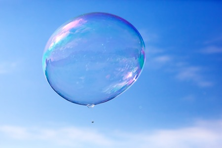 One clean soap bubble flying in the air, blue sky. Sun reflection