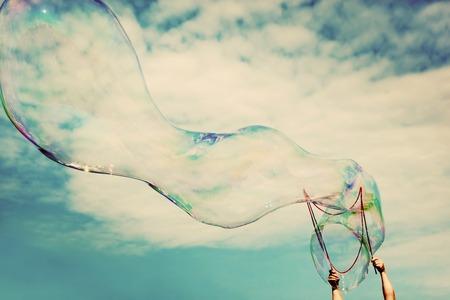 Blowing große Seifenblasen in der Luft. Weinlese-Freiheit, Sommer Konzepte. Geschwollene Wolken Himmel.