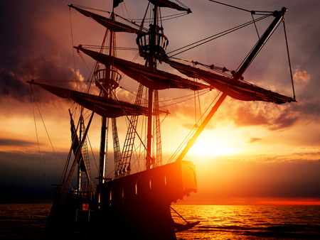 historical battle: Old ancient pirate ship on peaceful ocean at sunset. Calm waves reflection, sun setting.