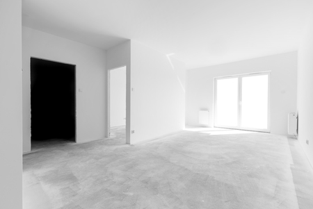 redecoration: Empty new apartment rooms for interior arrangement. Light from the windows, white walls, concrete floor Stock Photo