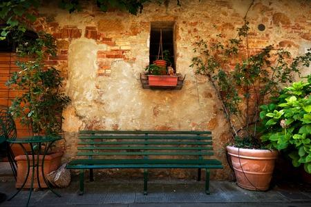 피엔, 이탈리아의 작은 마을에서 옛 이탈리아어 집 밖에 레트로 벤치입니다. 식물 장식, 빈티지 스톡 콘텐츠