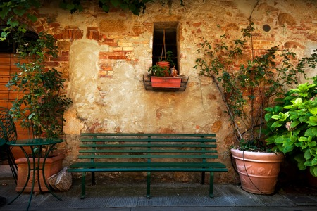 Retro bench outside old Italian house in a small town of Pienza, Italy. Plants decorations, vintage