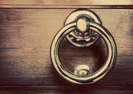doorknocker: Antique golden door knocker on wooden door. Vintage, retro background
