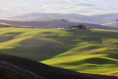 san quirico d'orcia: Tuscany landscape at sunrise. Typical for the region tuscan farm house, green hills, vineyard. Italy