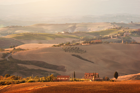 san quirico d'orcia: Tuscany landscape at sunrise. Typical for the region tuscan farm house, hills, vineyard. Italy Stock Photo
