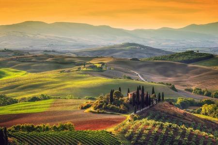 пейзаж: Тоскана пейзаж с восходом солнца. Типичный для региона тосканской ферме дома, холмы, виноградники. Италия Редакционное