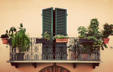 Retro romantischen Balkon mit Pflanzen und Blumen in Töpfen. Fenster mit grünen Verschluss. Alte italienische Haus in einer kleinen Stadt von Pienza, Italien. Jahrgang