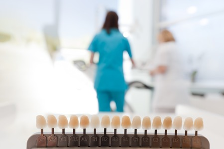 dentist's office: Sampler with teeth shades in dentists office. Dentist at work. Dentistry, clinic, teeth whitening Stock Photo