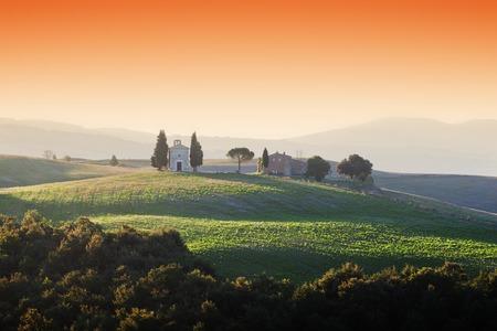 red sky: Tuscany landscape at sunrise with a little chapel of Madonna di Vitaleta, San Quirico dOrcia, Italy Stock Photo