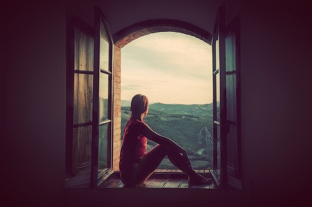 Young woman sitting in an open old window looking on the landscape of Tuscany, Italy. Conceptual romantic, dreaming, hope, travel.