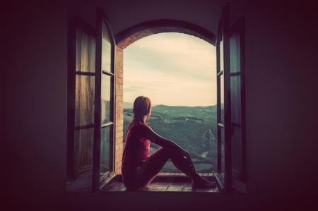 Jovem mulher sentada em uma janela velha aberta, olhando a paisagem da Toscana, Itália. Romântico conceitual, sonhando, esperança, viagens.