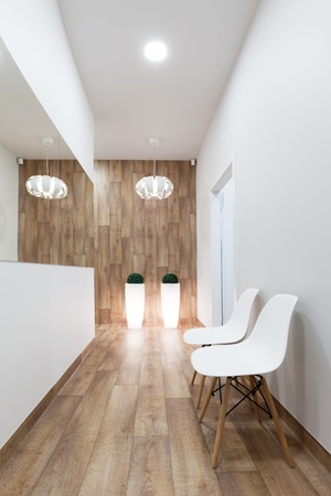 Modern waiting room, reception. Cozy minimalistic interior with seats, lights, mirror and parquet floor.