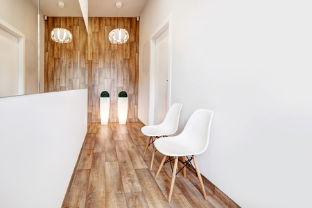 work area: Modern waiting room, reception. Cozy minimalistic interior with seats, lights, mirror and parquet floor.