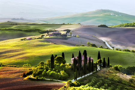 agriturismo: Tuscany landscape at sunrise. Typical for the region tuscan farm house, hills, vineyard. Italy Stock Photo